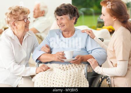 Lächelnd gelähmt Senior Frau zwischen glücklicher Freund und Krankenschwester - Stockfoto