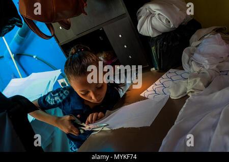 Eine salvadorianische Näherin schneidet einen weißen Stoff, mit der natürlichen blue Indigo gefärbt, danach in einem Kleidung Workshop in Santiago Nonualco, El Salvador. - Stockfoto