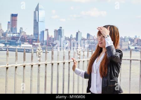 Asiatische Frau in Leder Jacke vor der Skyline der Stadt stehend - Stockfoto