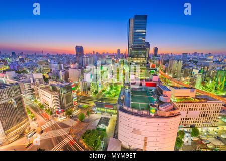 Shibuya, Tokio, Japan, über die berühmte Skyline der Stadt jagt Zebrastreifen in der Abenddämmerung. - Stockfoto