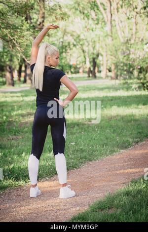 Porträt der schönen jungen Frau trainieren in den Park. Kaukasische Frauen Fitness Modell in den Morgen arbeiten. in Sportkleidung gekleidet. - Stockfoto