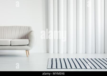 Gemütliche weiß Sofa und einem gestreiften Teppich in ein stilvolles ...