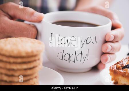 Nahaufnahme von einem kaukasischen Mann mit weißer Keramik Tasse mit Kaffee in seinen Händen, mit dem text Ich liebe dich Papa geschrieben, an einem Tisch für breakfa eingestellt - Stockfoto
