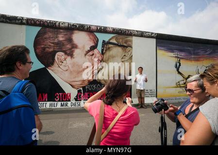 Berlin. Deutschland. Touristen posieren für Fotos vor einem der übrigen Abschnitte der Berliner Mauer an der East Side Gallery. Touristen posieren für ph - Stockfoto
