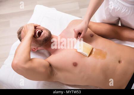 Ansicht des jungen Mannes zu schreien, während das Einwachsen der Brust in Spa. - Stockfoto