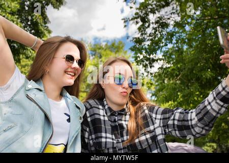Zwei schöne Frau nimmt selfie durch Smart Phone im Park - Stockfoto