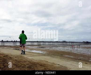 Southport, Merseyside, England. 22. August 2015. Jogger läuft entlang der Strandpromenade an einem bewölkten warmen - Stockfoto