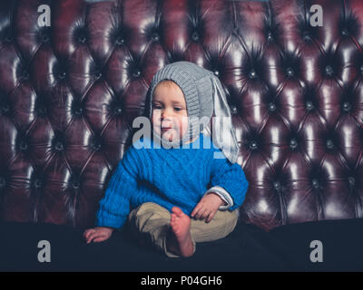 Einen niedlichen kleinen Jungen tragen ein Häschen Hut sitzt auf einem Sofa - Stockfoto