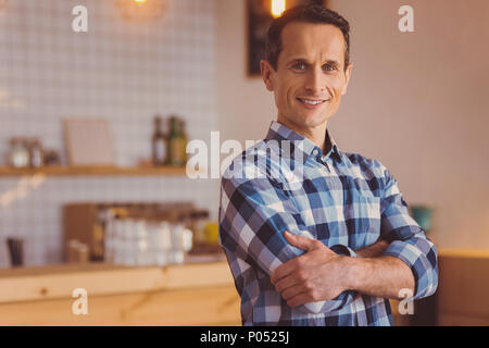 Die jungen Besitzer in seinem Café mit Waffen posiert gekreuzt - Stockfoto