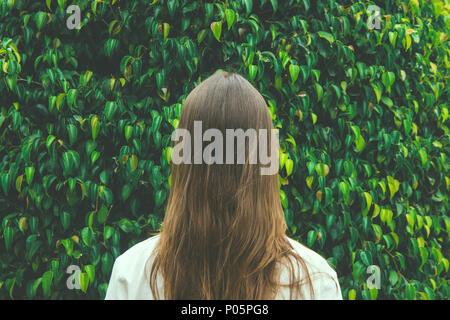Junge kaukasier Frau Mädchen mit langen kastanienbraunen Haare stehen mit Zurück zum Viewer auf dem grünen Wald Baum Laub Hintergrund. Kontemplation Ruhe Min. - Stockfoto
