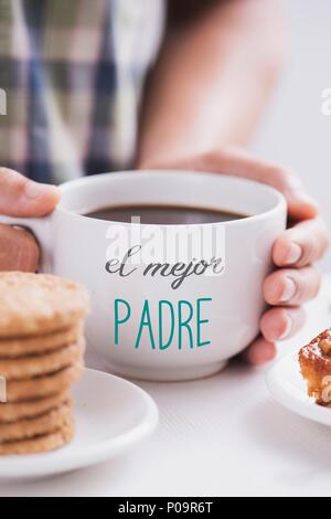 """Nahaufnahme von einem kaukasischen Mann mit weißer Keramik Tasse mit Kaffee in seinen Händen, mit dem Text 'el mejor Padre"""", """"der beste Vater"""" auf Spanisch geschrieben, an - Stockfoto"""