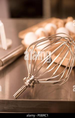 Nahaufnahme der Schneebesen und rohe Eier für die Creme auf Zähler im Restaurant - Stockfoto