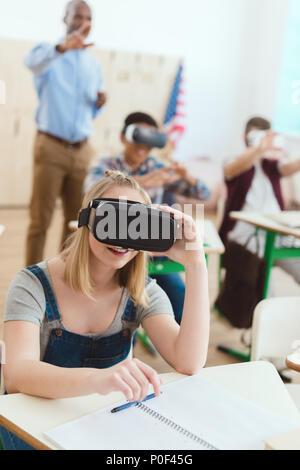 Teenage Schulmädchen mit Virtual reality Headset mit männlichen Mitschüler und Lehrer hinter