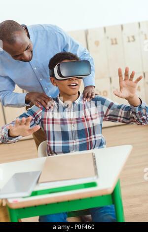 Afrikanische amerikanische Lehrer halten Schultern bei der Verwendung von Virtual Reality headset Schüler - Stockfoto
