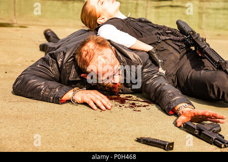 Klled Frau als Special Agent ausgestattet liegt auf einem Mann im Blut, er zieht seine Hand in Richtung der Waffe - Stockfoto