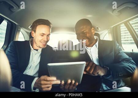 Zwei lächelnde Kollegen mit einem digitalen Tablet zusammen, während auf dem Rücksitz eines Autos durch die Stadt fahren Sitzen - Stockfoto