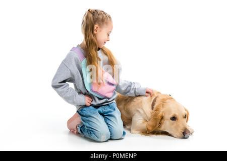 Stilvolle Kind streicheln Liegender Hund mit Halsband isoliert auf weißem - Stockfoto