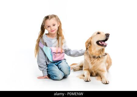 Portrait von wenig glückliches Kind mit Hund liegend neben auf Weiß isoliert - Stockfoto