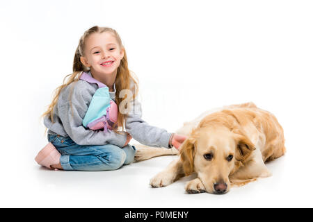 Lächelnd Kind berühren beige dog Isolated On White - Stockfoto