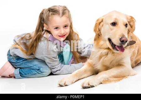 Detailansicht der lächelnden kleines Kind mit liegend beige dog Isolated On White - Stockfoto