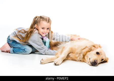 Portrait von glückliches Kind berühren liegend beige dog Isolated On White - Stockfoto