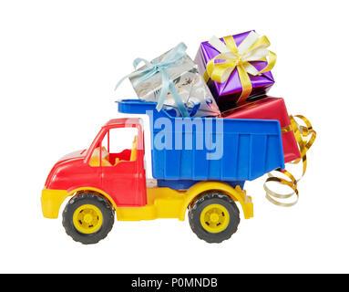Mehrfarbige Kunststoff Spielzeug Lkw liefert viele Geschenkboxen mit dekorativen Bändern im Körper gebunden, auf weißem Hintergrund - Stockfoto