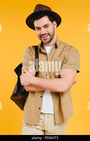 Hübscher junger Mann in Hut stand mit verschränkten Armen und lächelnd in die Kamera isoliert auf Gelb - Stockfoto