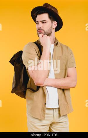 Nachdenkliche junge männliche Reisende stehend mit der Hand am Kinn und weg schauen auf gelb isoliert - Stockfoto