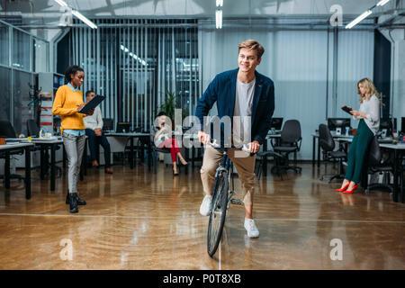 Glückliche junge Geschäftsmann Reiten Fahrrad an moderne Büro, während seine Kollegen arbeiten - Stockfoto