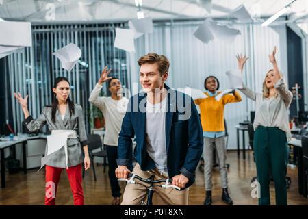 Junge Unternehmer Reiten Fahrrad im Büro, während Partner werfen Papiere auf Hintergrund - Stockfoto