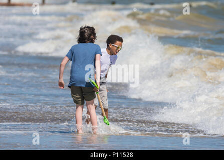 Paar Jungen an einem Strand am Meer spielen, wie die Wellen in der Nähe in England, Großbritannien. Jungen look unterschiedlicher ethnischer Herkunft zu sein. - Stockfoto
