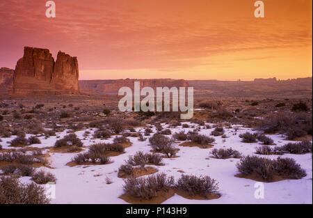 Arches National Park: In der Nähe von Moab, Blick auf den Canyon und Felsformationen über Schnee bedeckte Wüste in der Dämmerung mit cloudscape, Utah, USA - Stockfoto