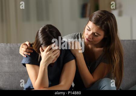 Jugendlich tröstlich hes traurig Freund in der Nacht auf einer Couch im Wohnzimmer zu Hause sitzen - Stockfoto