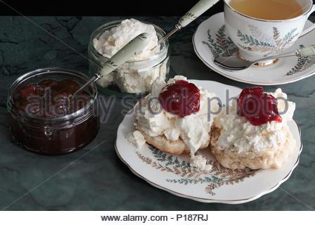 Eine creme Kaffee im Devon Stil, Scones mit Sahne mit Erdbeermarmelade auf der Oberseite und eine Tasse Gold Blend Kaffee, serviert auf Bone China tablewar - Stockfoto