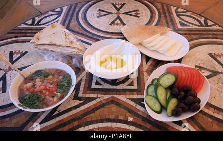 Ein libanesisches Frühstück Setup auf einem Mosaik Tisch. Die verschiedenen Gerichte sind Labneh, Foul mdammas, Halloumi Käse und Oliven, Gurken und Tomaten - Stockfoto