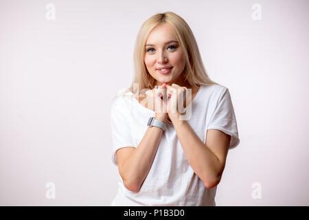 Fröhliche blonde Frau mit geballten Fäusten in der Nähe der Brust träumen - Stockfoto