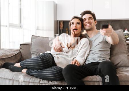 Portrait von ein glückliches junges Paar entspannt auf einer Couch zu Hause während des Fernsehens - Stockfoto