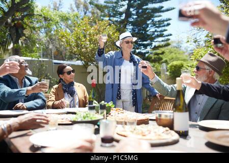Gerne ältere Frau toasten Wein mit Freunden bei Sunny Garden Party - Stockfoto