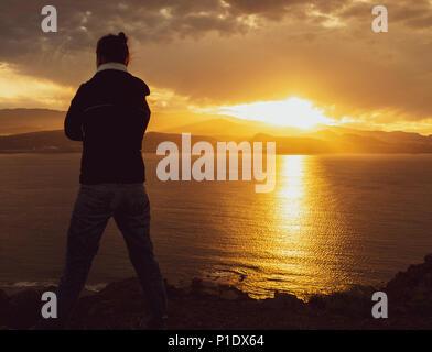 Rückansicht der Frau mit Blick auf das Meer von hohen Klippen bei Sonnenuntergang. Weibliche psychische Gesundheit/Depression, psychische Krankheit, Einsamkeit..., Konzept Bild - Stockfoto