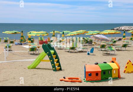 Spielplatz am Strand mit Sonnenschirmen und Liegestühlen im Sommer im Holiday Village - Stockfoto