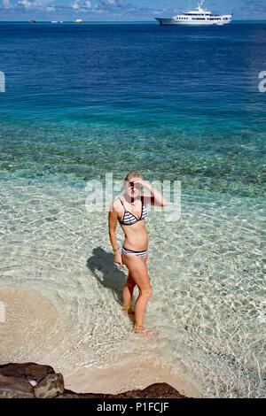 Bikini bekleidete Frau in den unberührten tropischen Gewässern auf Paul Gauguin Kreuzfahrt im Huahine Island - Stockfoto