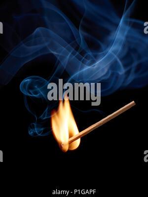Streichholz mit Flammen und Rauch im Moment der Zündung - Stockfoto