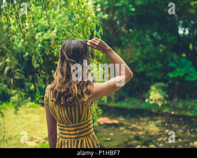 Eine modische Frau trägt ein Kleid steht ein Teich in einem Garten - Stockfoto