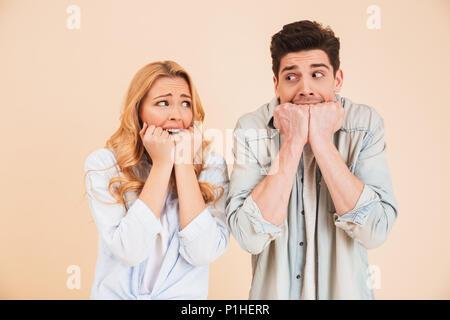 Bild von Angst, Mann und Frau in der Kleidung an einander suchen und Beißen ihre Fäuste emotional über beigen Hintergrund isoliert - Stockfoto
