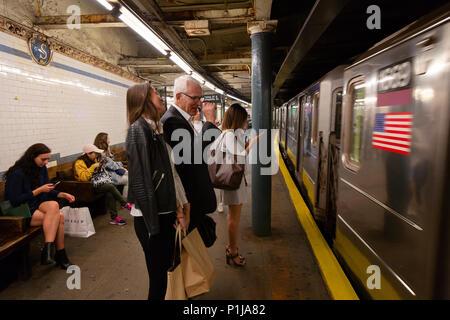Passagiere auf einem Bahnsteig warten, da die U-Bahn Zug kommt, die New Yorker U-Bahn, New York City, USA - Stockfoto