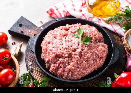 Hackfleisch in schwarzen Eisenplatte mit Zutaten zum Kochen. - Stockfoto