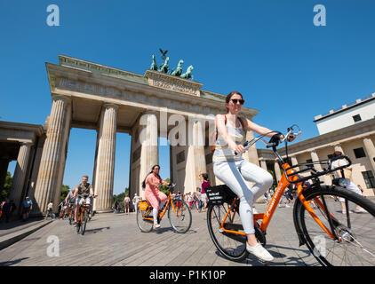 Touristen auf Fahrrädern vor dem Brandenburger Tor in Berlin, Deutschland - Stockfoto