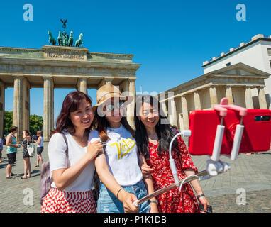 Chinesische Touristen mit selfie Stick vor dem Brandenburger Tor in Berlin, Deutschland - Stockfoto