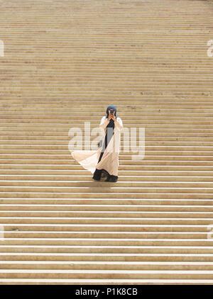 Frau im langen Kleid auf die Schritte des Parlaments eine selfie, Valletta, Malta - Stockfoto