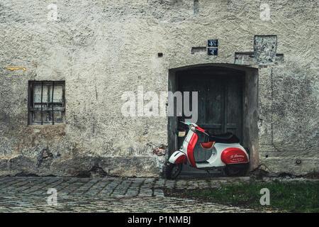 Füssen, Deutschland - 10. Mai 2018: Classic rot weiß und grün gefärbten Piaggio Vespa Roller Motorrad stehend auf einem Kopfsteinpflaster bedeckt Straße am d - Stockfoto